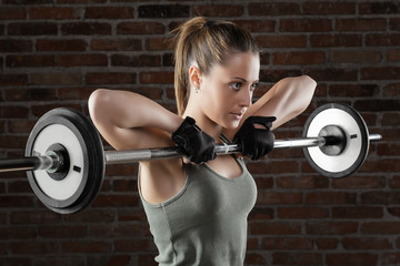 Young fit woman lifting dumbbells on brick background