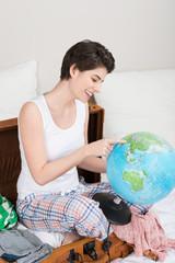 frau plant eine reise und zeigt auf den globus