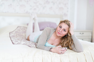 Beautiful young  woman relaxing on bed using smart phone