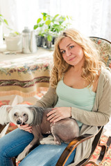 woman and chinese crested dog in rocking-chair