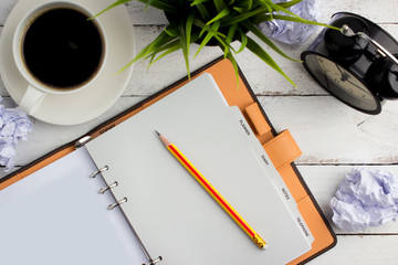 Top view of coffee on office table with notebook and pencil