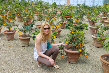 Girl near the potted plants in nursery citrus