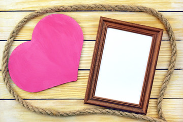 Heart and photo frame on the background of wooden boards
