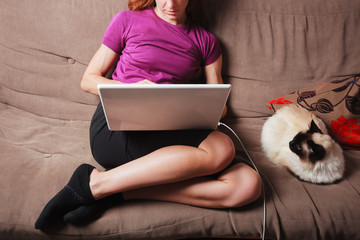 Young woman using laptop computer with cat next to her