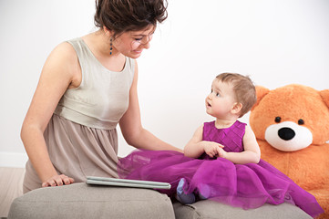 Mother and her curious daughter in violet dress with teddy bear