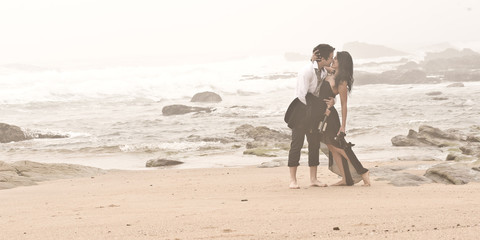 Young attractive couple kissing on beach through the mist
