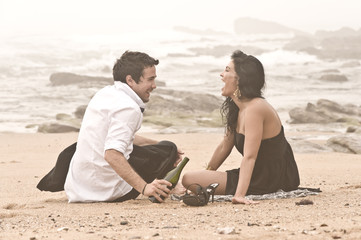 Young beautiful couple sharing a moment on beach with wine