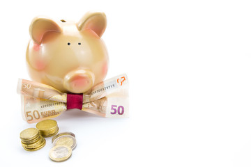 Piggy bank with a banknote bow and coins isolated