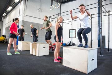 Crossfit group trains box jumps