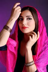 Beautiful oriental girl on dark colorful background
