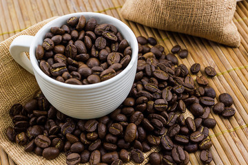Brown roasted coffee beans in coffee cup.