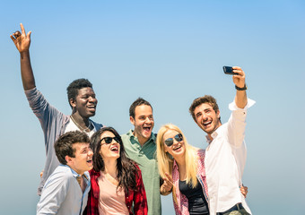 Group of multiracial friends taking a selfie on the blue sky