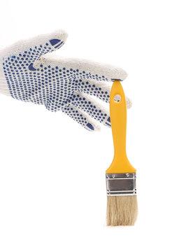Hand in gloves holds brush.