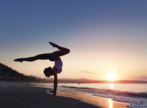 A woman doing a yoga handstand at the beach during a sunrise