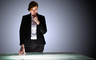 Redhead businesswoman standing and thinking by a desk