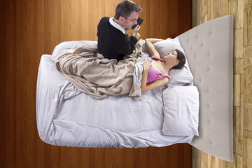 young dad tutoring sick daughter laying in bed
