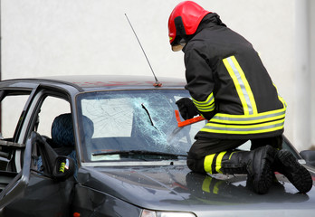 Fireman with work gloves while breaking a car windshield to rele