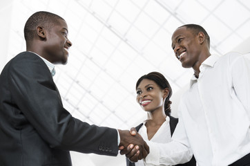 Three african business people handshake