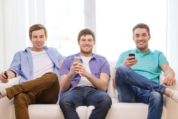 smiling friends with smartphones at home