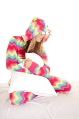 woman in colorful pajamas sit with pillow look down