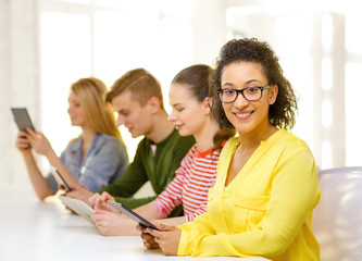 smiling female students with tablet pc at school