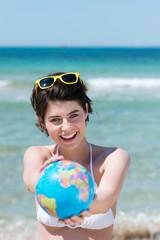 lachende frau am strand zeigt globus