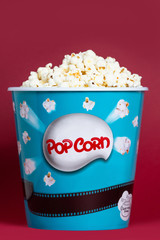 Popcorn in cardboard box for cinema, isolated on red background.