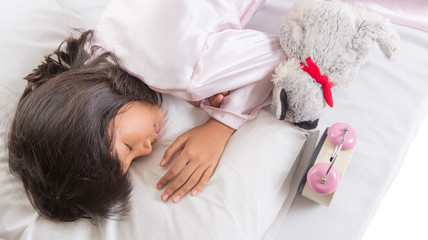 Young Asian Malay girl sleeping with alarm clock on her side