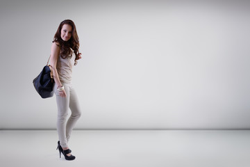 Beautiful young fashion woman posing at studio with bag, full le