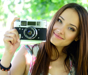 Cheerful beautiful girl talking pictures with vintage camera