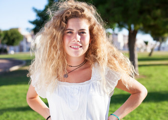 young blond woman standing at park on sunny day