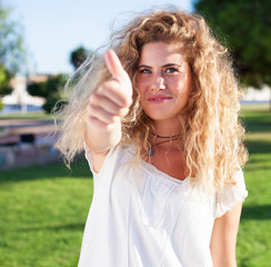 young woman with thumb up at park on a sunny day