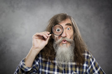 Senior old man looking through zoom magnifying glass, amazement