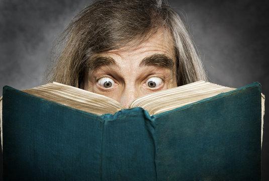 Senior reading open book, suprised old man,  amazing eyes