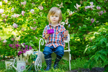 Kid relaxing and having a snack in the blooming garden