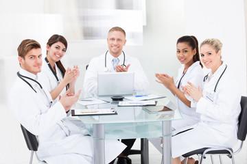 Confident Doctors Applauding At Desk