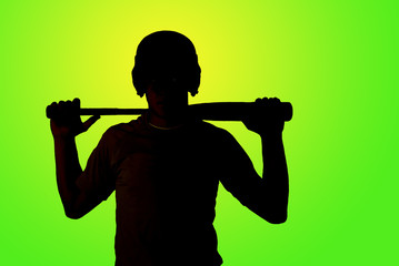 green background of silhouette of baseball player holding his ba