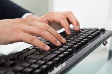 Businessman Using Computer Keyboard At Desk