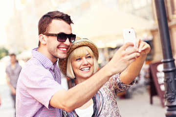 Happy couple taking a picture of themselves while sightseeing