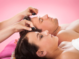 Couple Receiving Hot Stone Massage At Spa