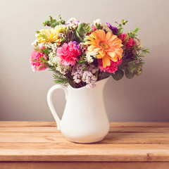 Flower bouquet in white jug on wooden table