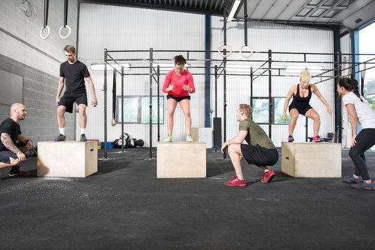 Crossfit group trains box jump