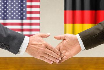 Vertreter der USA und Deutschlands reichen sich die Hand