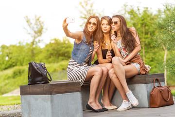 Three beautiful girlfriends make Selfie photo on a bench