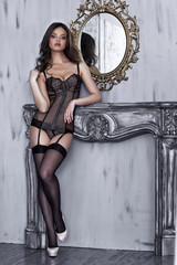 Beautiful alluring young woman in black sexy lingerie