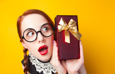 Redhead girl with gift on yellow background.