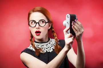 Redhead girl with retro camera on red background.