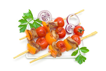 skewers of meat with vegetables on a plate isolated on a white