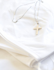 Silver cross on white cloth.