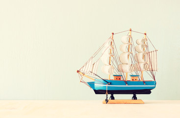 decorative boat over wooden textured background.